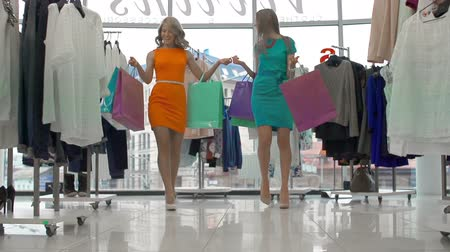 ubrania : Tilt down the ladies with shopping bags strolling along clothes store in slow motion
