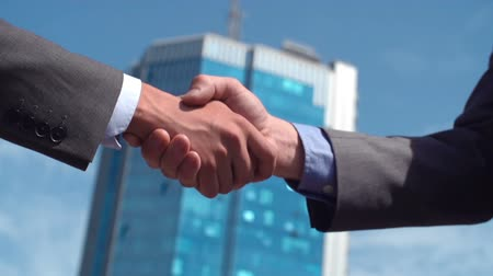 negocjacje : Low angle of two cropped businessmen shaking hands