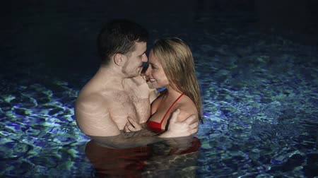 amantes : High angle of lovers cuddling in the swimming pool