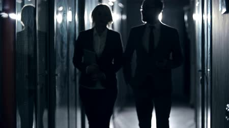 unrecognizable people : Business partners approaching camera walking along dark office corridor