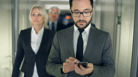 fejlesztése : Slow motion of business team approaching camera walking along business center corridor, focus on bearded Asian man with phone