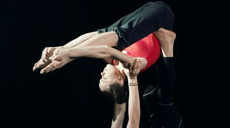 баланс : Tilt up of two partners practicing acroyoga