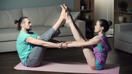 партнеры : Couple practicing in-home yoga performing double boat pose