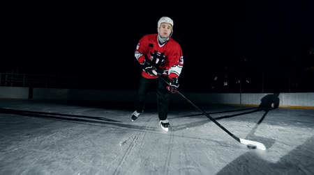 атлетика : Hockey player ice skating with l-shaped hockey stick pushing puck