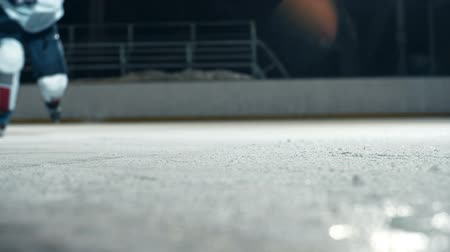 hockey rink : Low angle of hockey player running towards camera on skates and doing a turn cutting ice to powder Stock Footage
