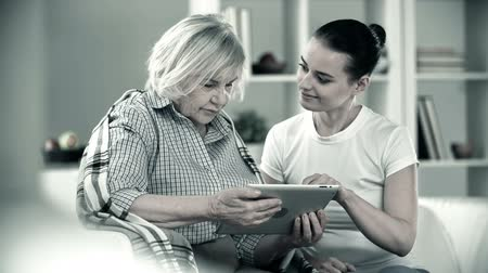 caregiver : Monochrome shot of young girl helping senior woman use the touchpad