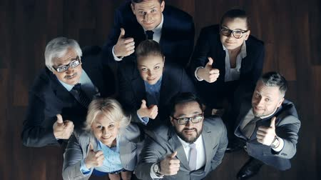 reconhecimento : Direct from above view of business team looking up at camera and showing appreciation gesture Vídeos