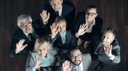 hét : Above view of seven business people waving at camera Stock mozgókép
