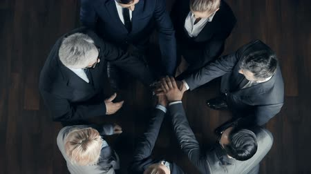 elkötelezettség : Right from above view of business team of seven team building putting hands on top of each other Stock mozgókép