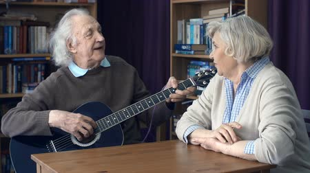 serenade : Close up of senior man singing to guitar for his sweetheart