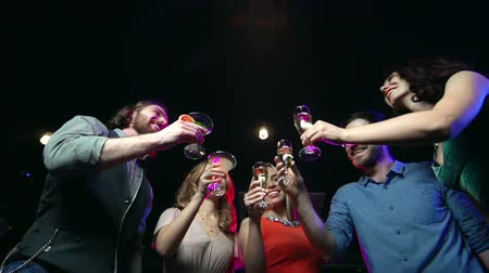despreocupado : Low angle of five friends raising glasses in toast standing at nightclub