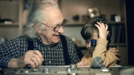 grandchild : Close up of little boy inspecting watch mechanism with eye loupe on