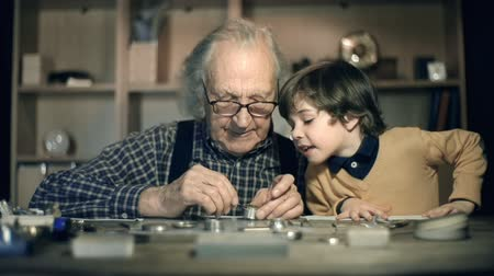 ремонтировать : Slow motion of clock master at work, his little grandson watching him mending mechanism