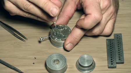 хозяин : Close up of unrecognizable master disassembling watch with special tools Стоковые видеозаписи