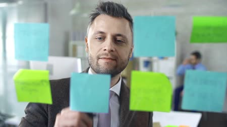 yazarak : Close up of smart businessman removing memory notes from the glass board and sticking new ones, his colleague in the background Stok Video