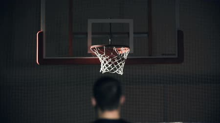 баскетбол : Rear view of unrecognizable man throwing a ball into the basket