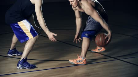 баскетбол : Low section of basketball player dribbling the ball, his opponent trying to rebound it