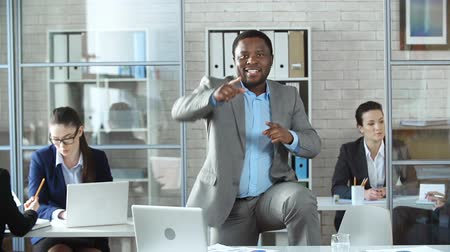 munka : Close up of Afro-American businessman standing in the middle of the office and dancing while his colleagues proceed to work ignoring him Stock mozgókép