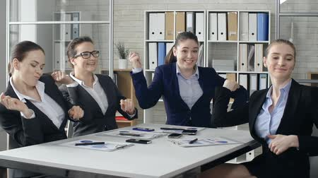 amalucado : Close up of four young colleagues performing exhilarated dance sitting at the office desk