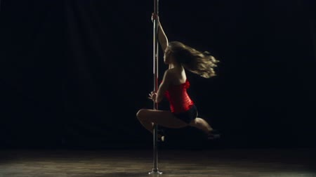 Slow motion of professional pole dancer spinning around the pole in the dark