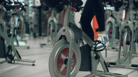 sınıf : Tilt up the unrecognizable girl doing cardio on gym cycling machine