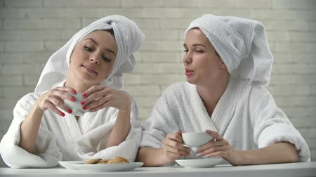 towel : Close up of girls in bathrobe with head wrapped in towel having tea