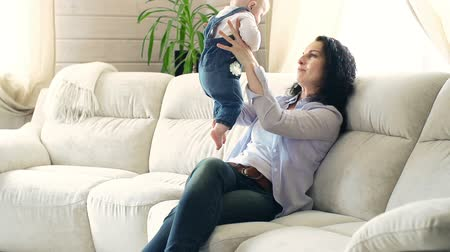 yapıştırma : Side view of woman sitting on the sofa with her adorable child