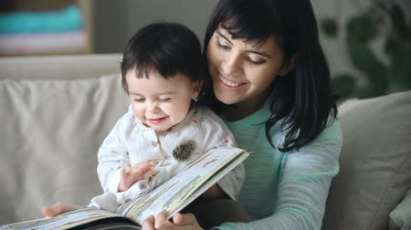 livros : Close up of baby sitting in the lap of her mother and turning the pages of illustrated book