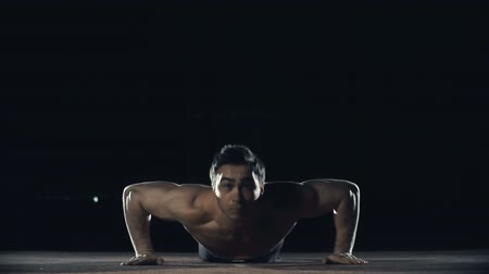 prone position : Front view of sportsman with torso performing explosive pushups clapping hands while in the air