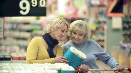 покупка товаров : Close up of two women picking toilet paper and putting it into shopping cart