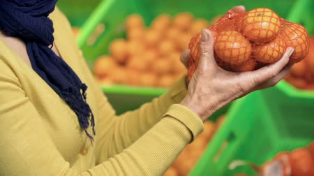 grocery : Cropped woman examining the tangerines