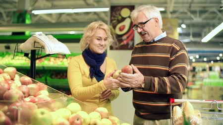 продукты : Close up of married couple picking apples in the shopping trolley full of products Стоковые видеозаписи