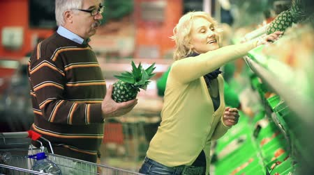 покупка товаров : Close up of man and woman choosing a pineapple