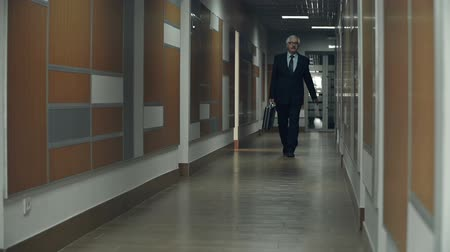 прихожая : Slow motion of business man approaching camera in the office hallway