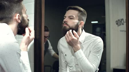 модный : Close up of man looking in the mirror and checking out his new beard style