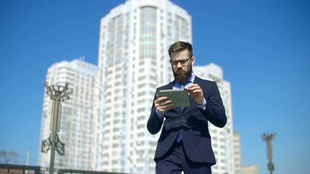 устройство : Smart businessman approaching camera walking along the street and browsing touchpad