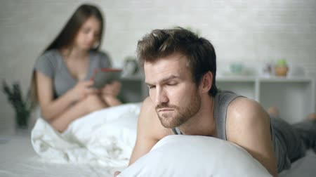 relação : Close up of man unhappy with his relationship with woman sitting in bed in with touchpad in the background Stock Footage
