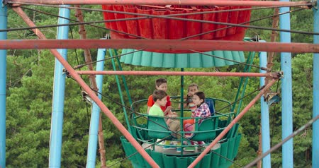 карусель : Four kids pointing at camera as they riding a Ferris wheel Стоковые видеозаписи