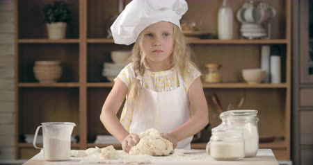 turta : Beautiful little girl kneading pastry dough in domestic kitchen