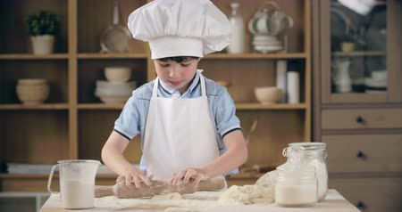 kötény : Kid wearing chef hat and apron rolling dough into circle in domestic kitchen