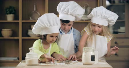 bakery : Three charming little bakers cutting out cookies of rolled dough Stock Footage