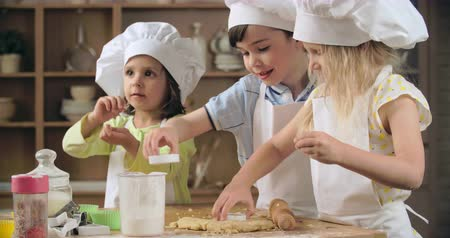 kötény : Group of preschoolers cutting out cookies in baking class