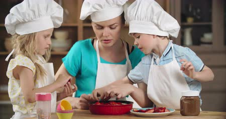 cakes : Mother and kids decorating cake with strawberry Stock Footage