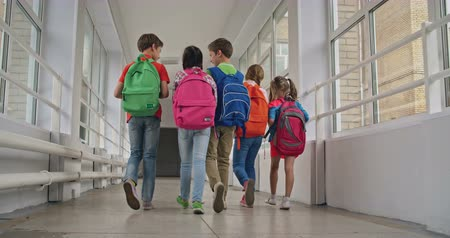 walking back : Rear view of school kids with backpacks walking along corridor
