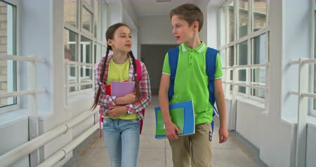 прихожая : Lovely schoolboy and schoolgirl chatting while walking down hallway
