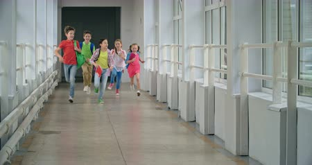 Excited pupils running down school corridor towards camera Vídeos
