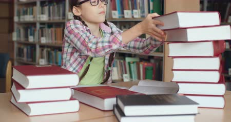 домашнее задание : Smart schoolgirl in eyeglasses doing research in library Стоковые видеозаписи