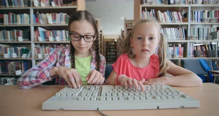 könyvtár : Two cheerful little schoolgirls typing on computer keyboard in school library