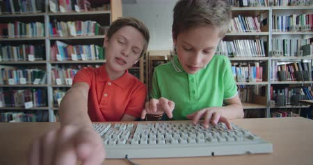 educar : Twin brothers arguing while typing on computer keyboard at school
