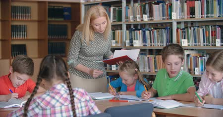 könyvtár : Experienced teacher working with elementary students in literature class